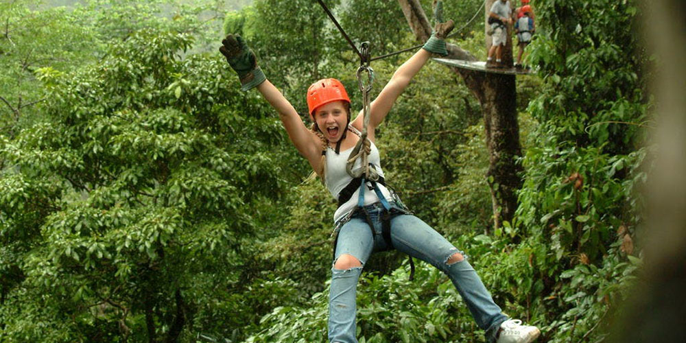 Girl zip lining in jungle