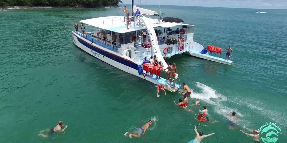 People swimming beside catamaran